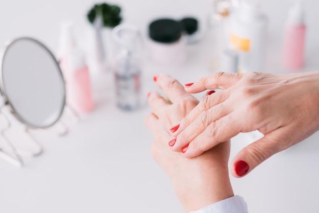 Tratamento de beleza. produtos para a pele das mãos da idade. senhora idosa aplicando cosméticos caros.