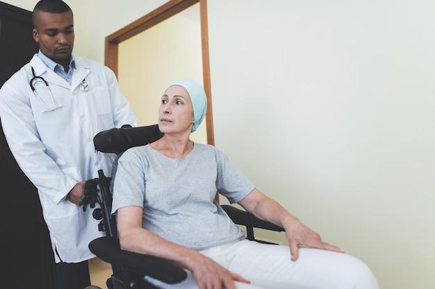 Tratamento de câncer. médico ajuda a mulher na cadeira de rodas.
