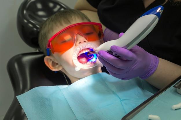 Tratamento de cárie moderno para uma criança. odontologia infantil. garotinho em óculos de proteção laranja. canal de tratamento de tratamento ou cárie.
