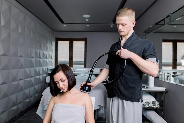 Tratamento de cavitação por ultra-som. jovem morena recebendo vibro massagem terapêutica no salão de beleza.