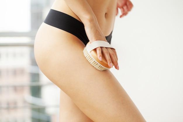 Tratamento de celulite, braço de mulher segurando o pincel seco no topo da perna