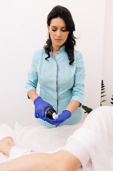 Tratamento de creme nas pernas da mulher com loção hidratante para prevenir a pele seca nas partes do corpo feminino