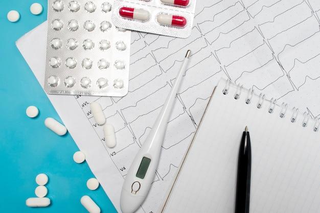 Tratamento de doenças cardíacas. miocárdico. acidente vascular encefálico. cardiograma de coração, caderno do médico e comprimidos
