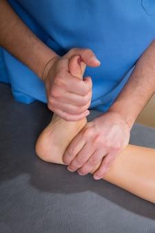 Tratamento de fisioterapia no tornozelo com mãos de terapeuta