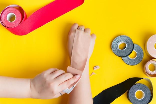 Tratamento de gravação cinesiologia com fita bege na mão feminina