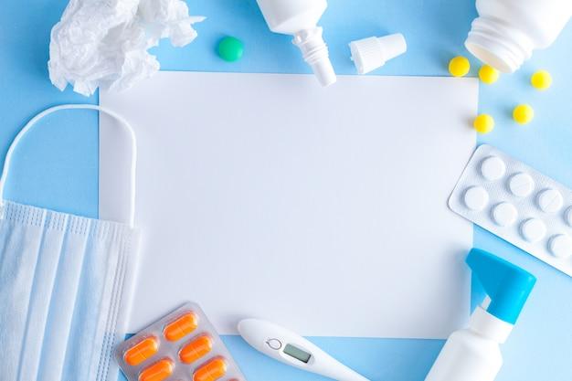 Tratamento de gripes e resfriados. vários medicamentos, um termômetro, brotam de um nariz entupido e uma dor de garganta. copie o espaço. medicina plana leigos.