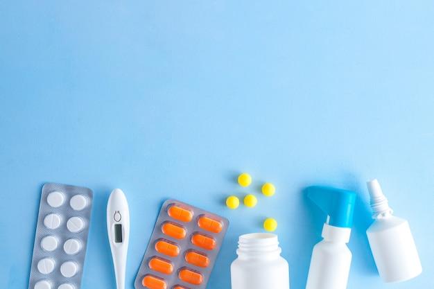 Tratamento de gripes e resfriados. vários medicamentos, um termômetro, brotam de um nariz entupido e uma dor de garganta em um fundo azul. medicina plana leigos.