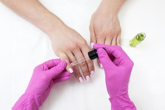 Tratamento de óleo na manicure. salão profissional cuidar de mãos e unhas closeup em fundo branco. massagem úmida como visão superior do procedimento de cuidados com a pele.