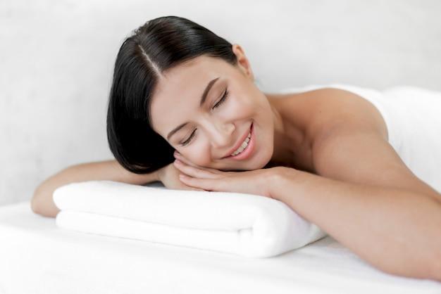 Tratamento de pele de beleza jovem bonita relaxante deitado na toalha no salão de massagem e spa