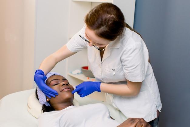 Tratamento de pele profissional. bela mulher africana bonita visitando um cosmetologista enquanto se importa com sua pele
