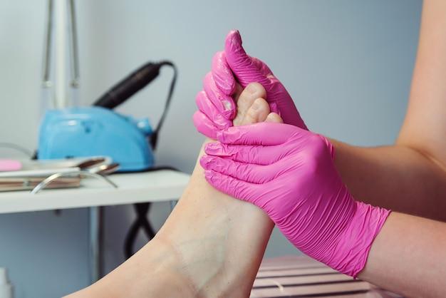 Tratamento de pés. tratamento de beleza para pernas. pedicure mestre massageando os pés com esfoliante.