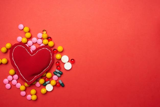 Tratamento de saúde de fundo vermelho de coração mole comprimidos multicoloridos