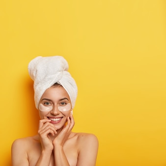 Tratamento de spa e conceito de higiene. mulher jovem e bonita com pele fresca e saudável, usa adesivos cosméticos sob os olhos, reduz o inchaço e as olheiras