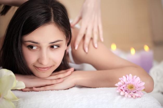 Tratamento de spa. mulher bonita, recebendo massagem de pedras no salão spa.