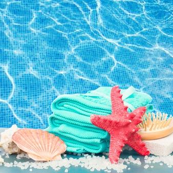 Tratamento de spa no mar com estrela do mar na mesa azul ao lado da piscina