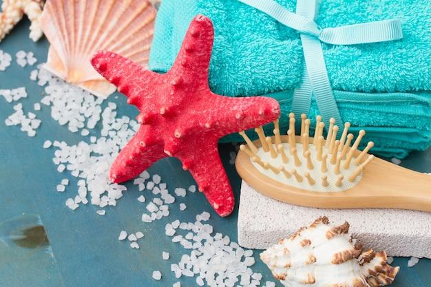 Tratamento de spa no mar com toalhas azuis e estrela do mar vermelha na mesa azul