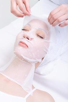 Tratamento de spa para rosto de mulher jovem em salão de beleza
