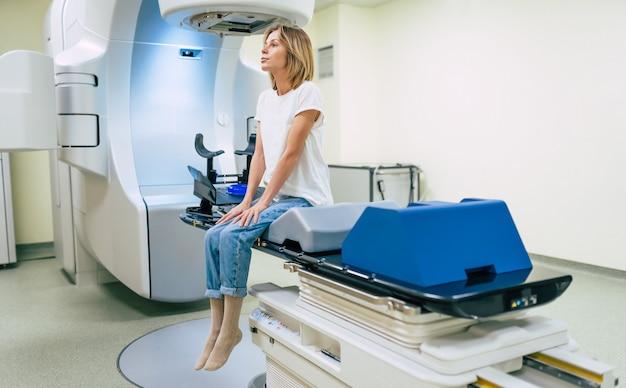 Tratamento do câncer em uma clínica médica privada moderna ou hospital com um acelerador linear. equipe de médicos profissionais trabalhando enquanto a mulher está se submetendo à radioterapia para câncer