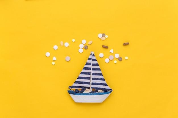 Tratamento do enjôo. veleiro e frasco de comprimidos em fundo amarelo. vista do topo