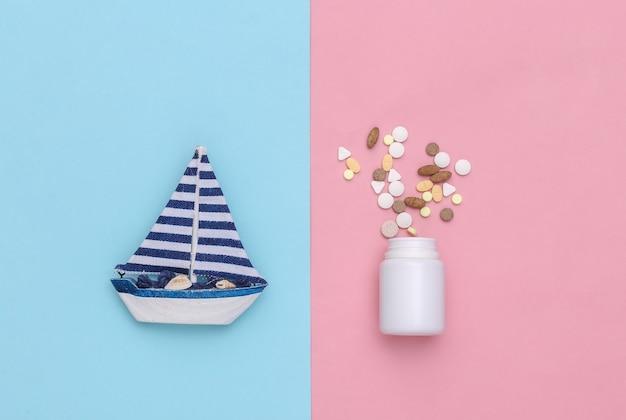 Tratamento do enjôo. veleiro e frasco de comprimidos em fundo azul-rosa pastel. vista do topo