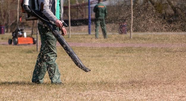 Tratamento do relvado. o jardineiro remove a grama seca velha do gramado no parque com um soprador portátil a gasolina.