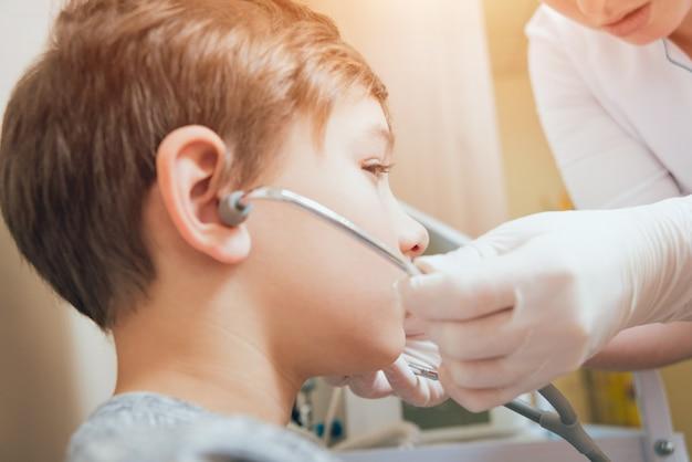 Tratamento e aquecimento dos ouvidos de um menino. pediatria moderna.