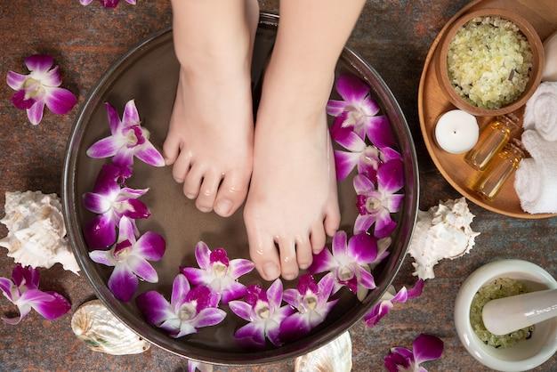 Tratamento e produto spa para pés e mãos femininas. flores da orquídea em uma tigela de cerâmica.