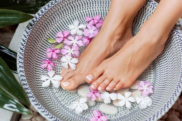 Tratamento e produto spa para pés femininos banho de pés em tigela com flores tropicais
