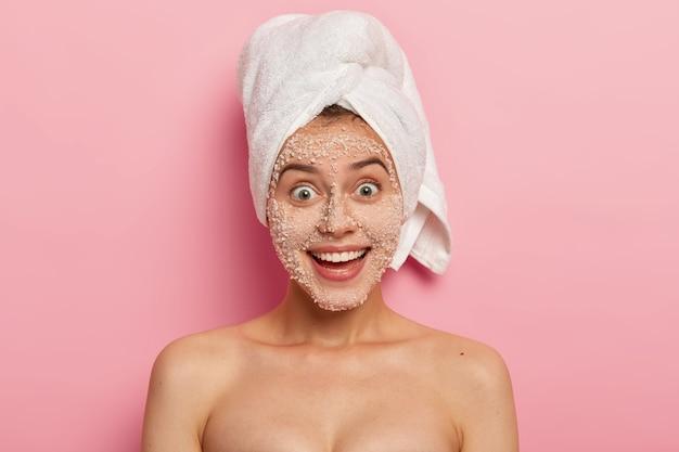 Tratamento facial. mulher adorável e feliz com sorriso charmoso, remove toxinas e cravos do rosto, aplica esfoliante natural de grânulos de sal branco marinho, arranca tamancos, tem corpo nu bem cuidado.