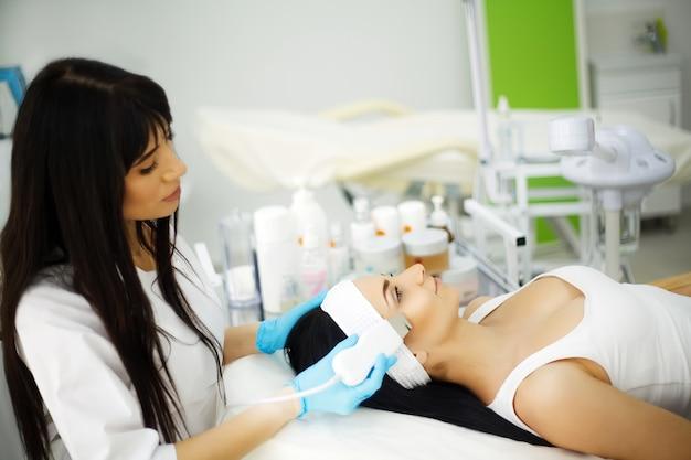Tratamento facial rejuvenescedor. modelo recebendo massagem terapia de elevação em um salão de beleza spa. esfoliação, rejuvenescimento e hidratação. modelo e médico. cosmetologia.
