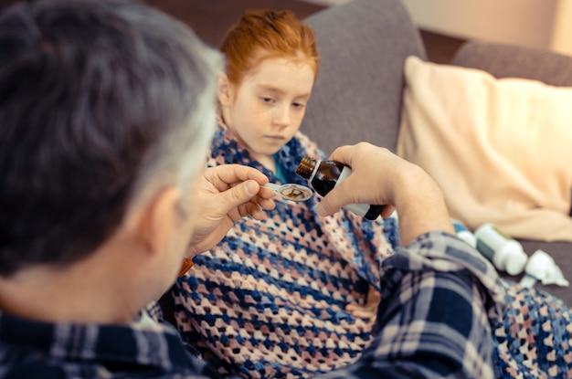 Tratamento médico. vista superior de uma colher com uma mistura para tosse sendo dada a uma bela garota doente