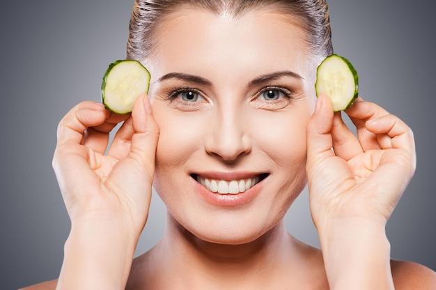 Tratamento natural de spa. linda mulher madura segurando pedaços de pepino perto dos olhos e sorrindo em pé, isolado no fundo branco