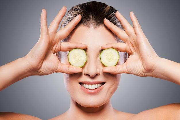 Tratamento natural de spa. mulher madura alegre segurando pedaços de pepino na frente dos olhos enquanto fica de pé, isolado no fundo branco
