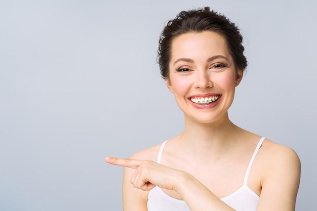 Tratamento ortodôntico. conceito de atendimento odontológico. sorriso saudável de mulher bonita close-up. closeup cerâmico e suportes de metal nos dentes. lindo sorriso feminino com aparelho.