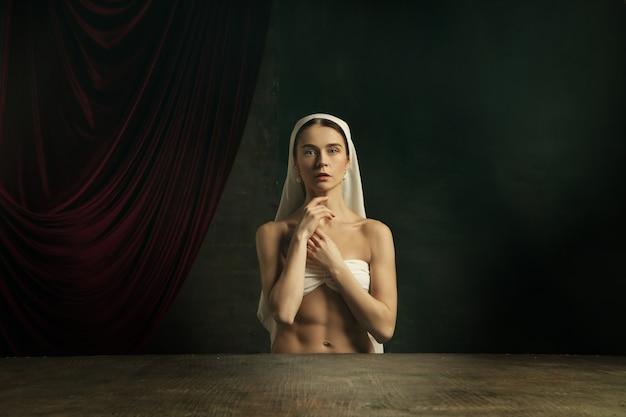 Tratamento. refilmagem moderna da arte clássica com o tema coronavírus - jovem mulher medieval em fundo escuro, medindo a temperatura, tomando comprimidos. conceito de coronavírus, pandemia, criatividade.