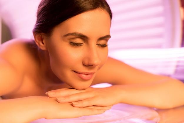 Tratamento solarium. close de uma jovem atraente deitada na cama de bronzeamento artificial e sorrindo
