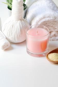 Tratamentos de spa com colher de sal, bola de ervas de compressão, velas e toalha
