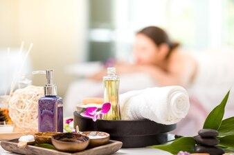 Tratamentos de spa com flores da orquídea no fundo da tabela do spa relaxante jovem