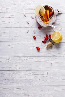 Tratar o frio. xícara com chá quente com limão e bagas fica em uma mesa