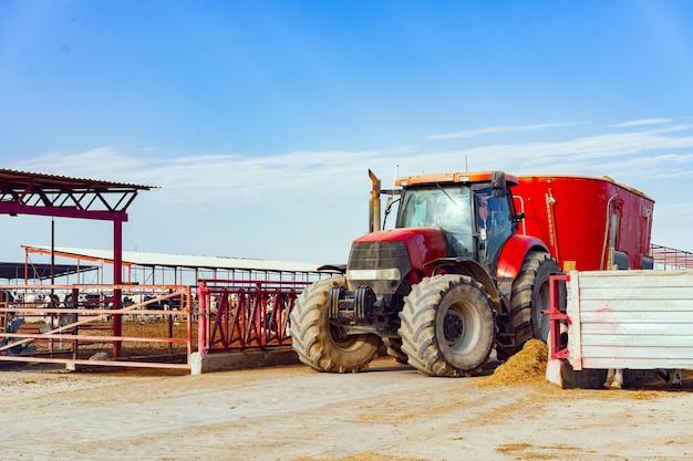 Trator agrícola vermelho moderno dirigindo em uma fazenda