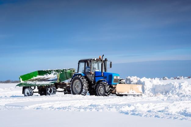 Trator azul com um trailer limpa a neve com uma pá