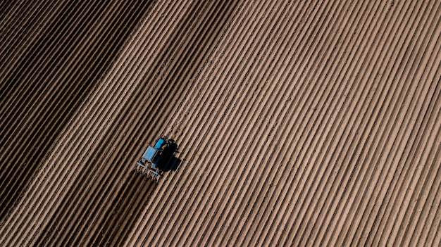 Trator azul que ara o campo. fotografia aérea com drone