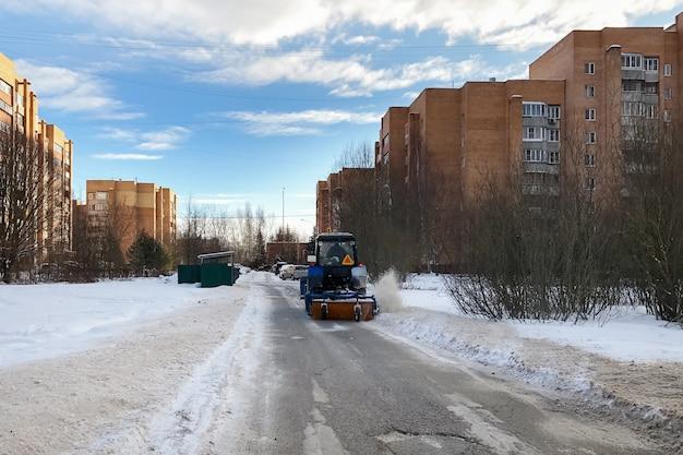 Trator com arado de neve com um soprador de neve limpa as ruas de uma área residencial no inverno