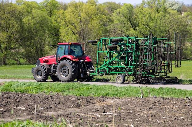 Trator com cultivador na estrada rural