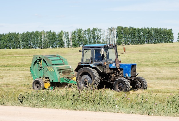 Trator com empilhador rebocado, produção de feno