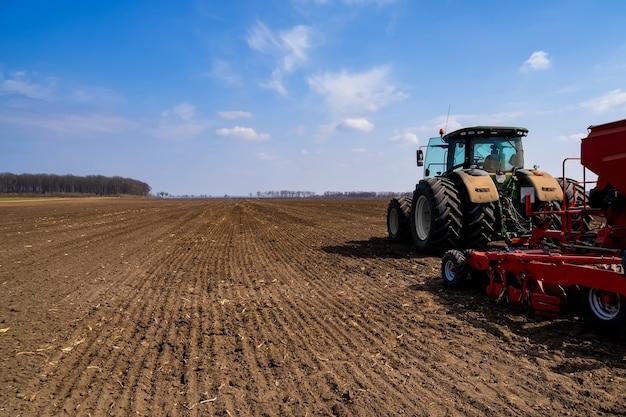 Trator com semeadora no campo no início da primavera