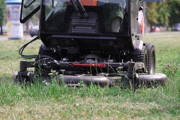 Trator cortador de grama cortando grama em serviços de close up do parque para cortar grama em áreas locais
