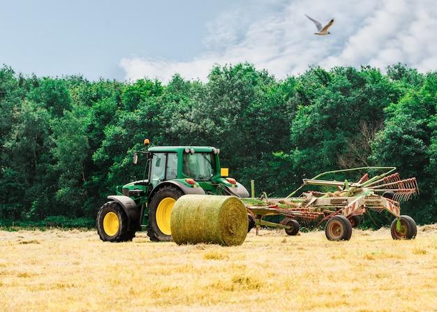 Trator cortando feno no céu de horário de verão e palheiros no campo