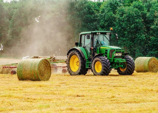 Trator cortando feno no verão contra um céu azul nublado, palheiros no campo