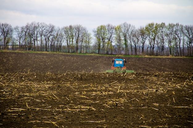 Trator cultivando campo na primavera